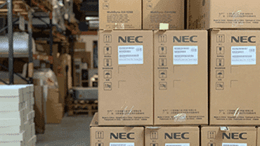 NEC boxes stacked up in a warehouse