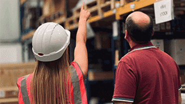 Woman in hard hat pointing to something in a warehouse, man standing next to woman looking at what she is pointing at